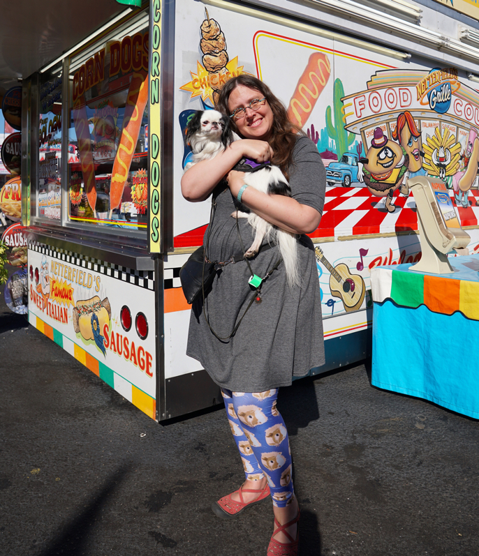 Veronica holds Hestia in front of a hot dog stand.