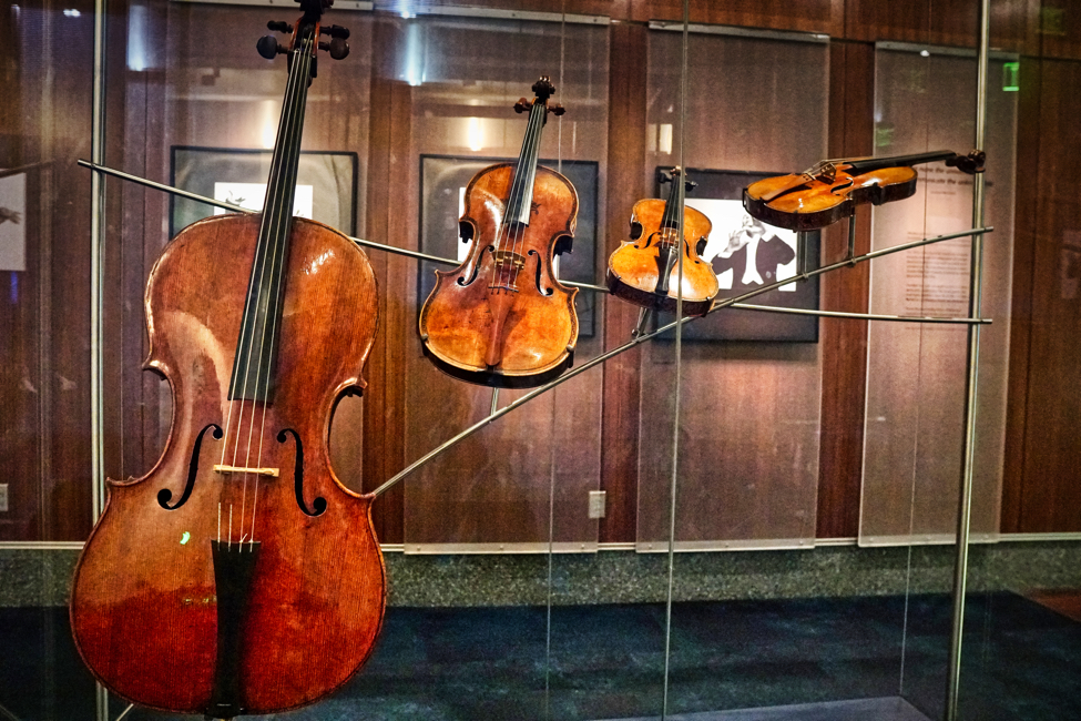 A cello, viola, and two violins are artistically displayed in a curving twist.