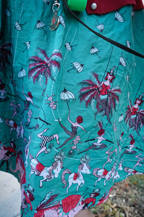 Veronica's dress has a minty green background.  Various circus performers are on the dress including a unicycling pink poodle, acrobats, horses, and elephants.