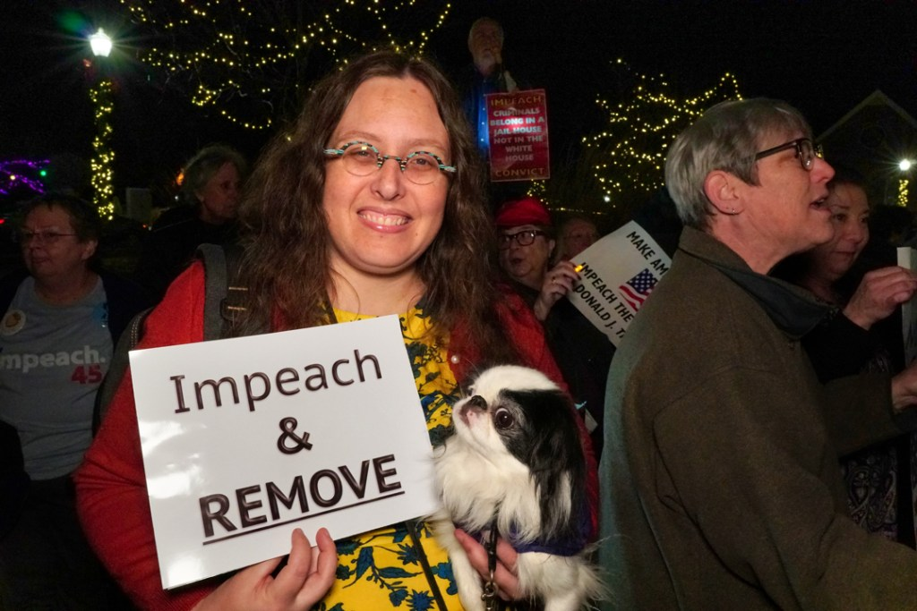 Veronica smiles, holding up her sign.  Hestia, who is in Veronica's arm, looks up as if she is reading the sign.