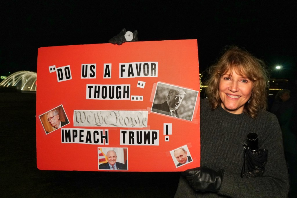 """Our friend Betsey holds up a sign that reads, """"'Do us a favor though...' We the people impeach Trump!"""""""