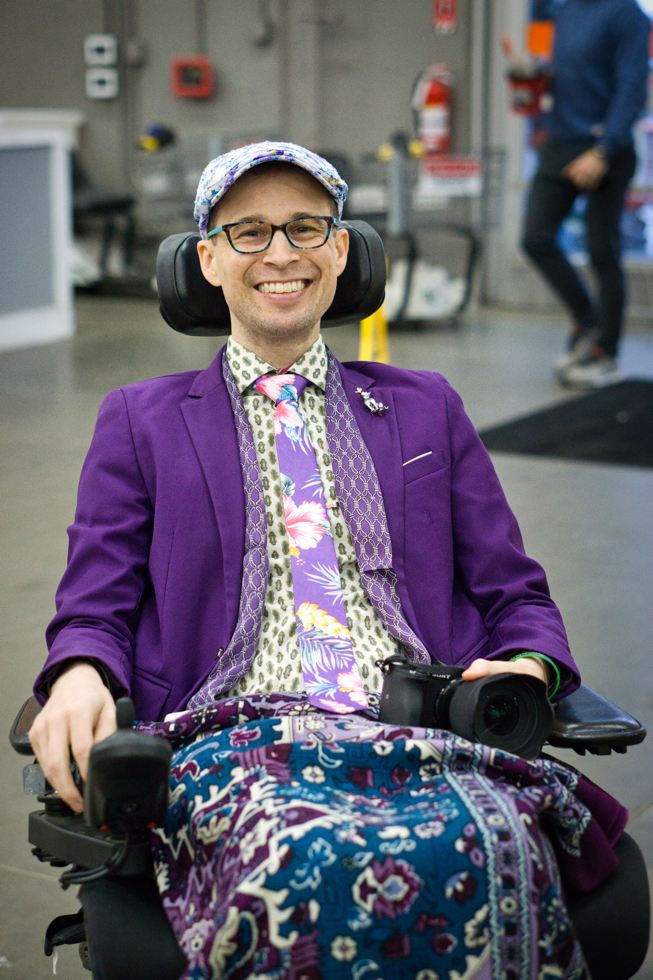 Brad shows off his very purple outfit and has a camera on his lap.