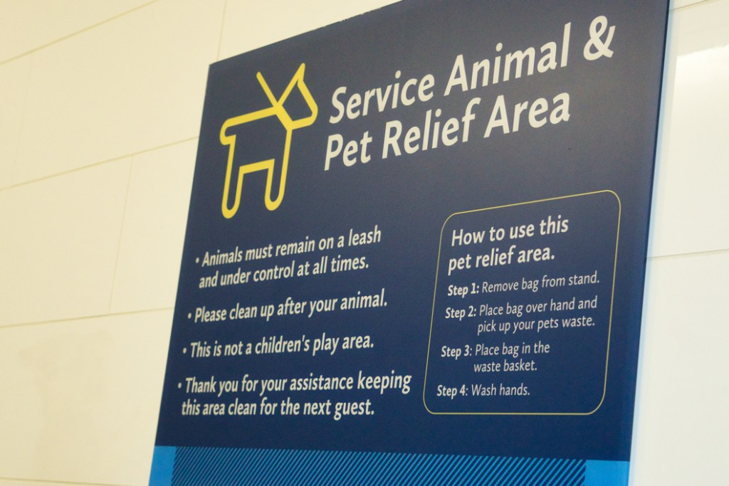 "A sign with instructions on how to use the service animal relief area.  It says, ""Step 1: Remove bag from stand.  Step 2: Place bag over hand and pick up your pets waste.  Step 3: Place bag in the waste basket.  Step 4: Wash hands."""