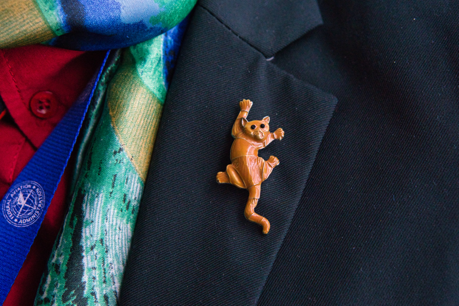 A closeup of Brad's pin.  It is an orange cat that looks like it's hanging onto Brad's blazer with its claws.