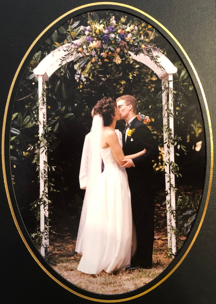 In front of a giant magnolia tree there is a white trellis with ivy and flowers covering it.  Veronica and Brad stand beneath it and kiss their first kiss as a married couple.