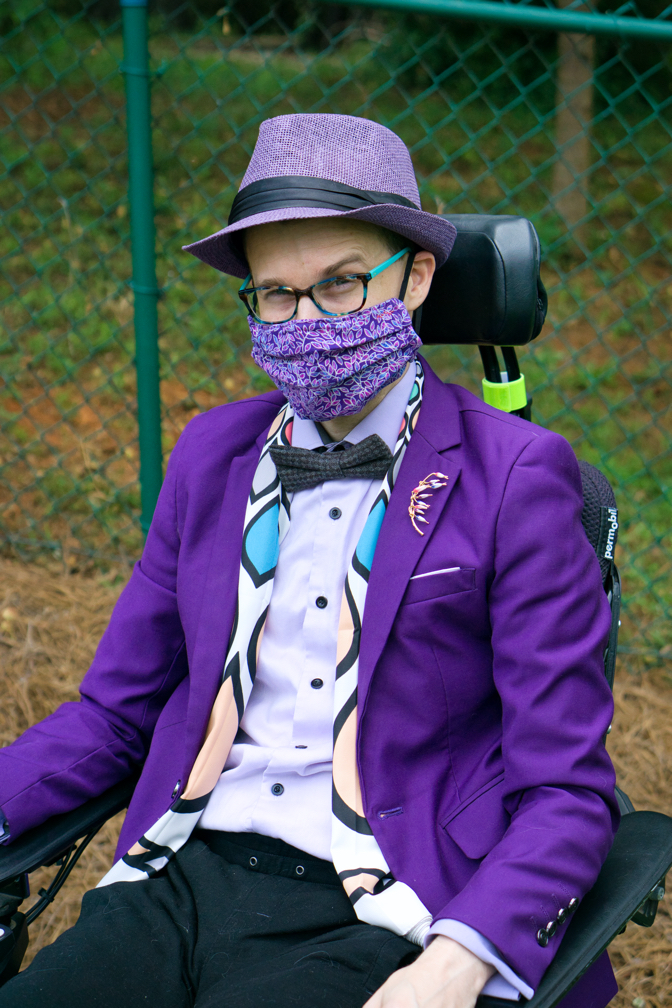 Brad wears a mask with a purple leaf pattern, a purple hat a white scarf with modern designs on it, and a brooch with purple and white flowers.