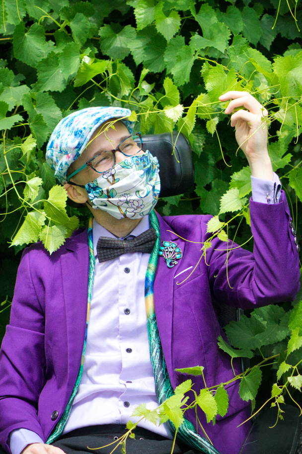 Amidst the vines, Brad wears a white mask with peacocks on it, a peacock scarf, a peacock pin, and a white lace hat with blue and purple flowers on it.