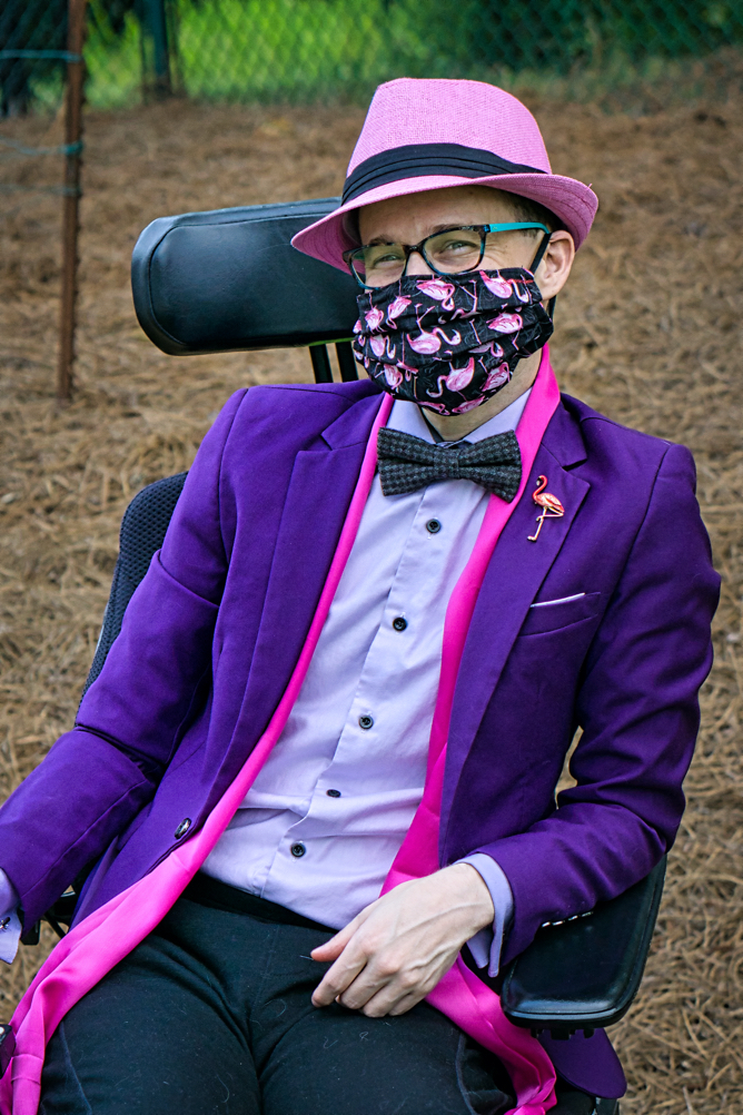 Brad wears a black mask with pink flamingos on it, a pink scarf, a pink flamingo pin, and a pink hat.