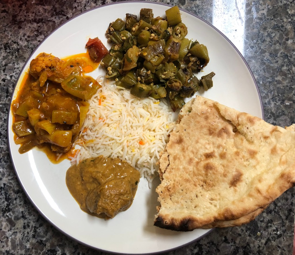 A plate of Indian food!  On the bottom is lamb kashmiri, the vegetable vindaloo is on the left, the bhindi bhaji is on the top, and the garlic naan on the right.  Rice is in the middle.