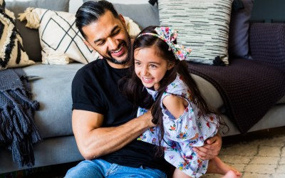 Documentary Family Photographers : Having cuddles with Daddy at home