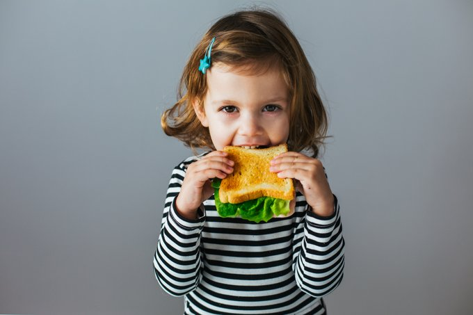 Young child eating a sandwich