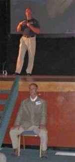 """El Dr. Steven Greer, en un momento de su """"actuacion"""" y su imperterrito guardaespaldas, guardando el acceso al escenario"""