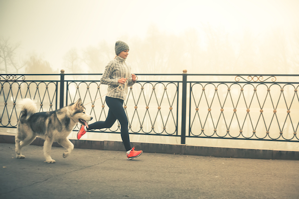 Woman running with dog by Shutterstock.