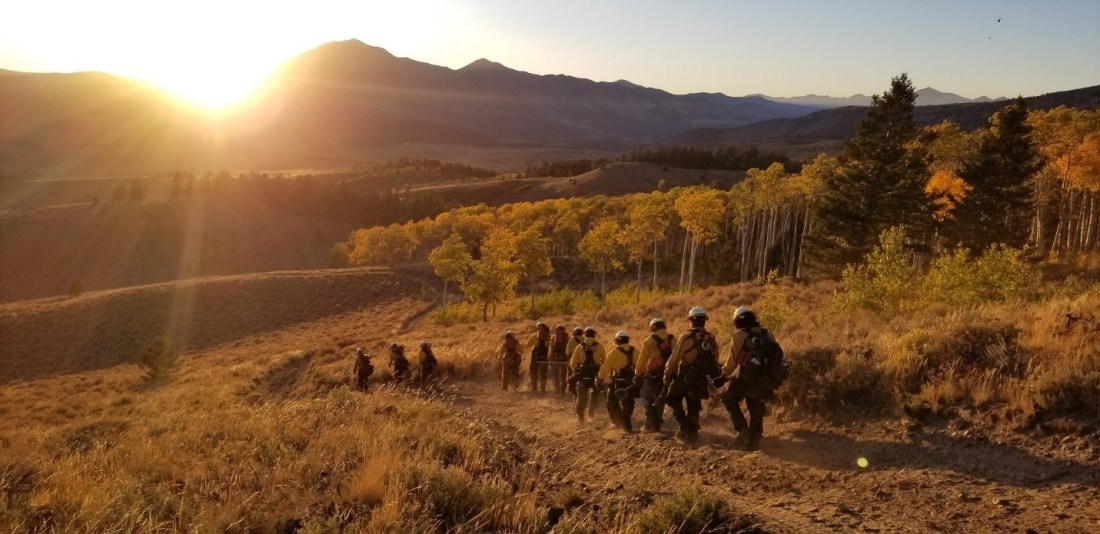 Hand crew walks toward the mountains at sunset.