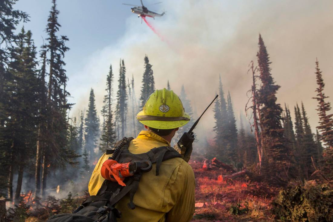 Firefighter holds a radio as a helicopter flies over the Rice Ridge Fire.