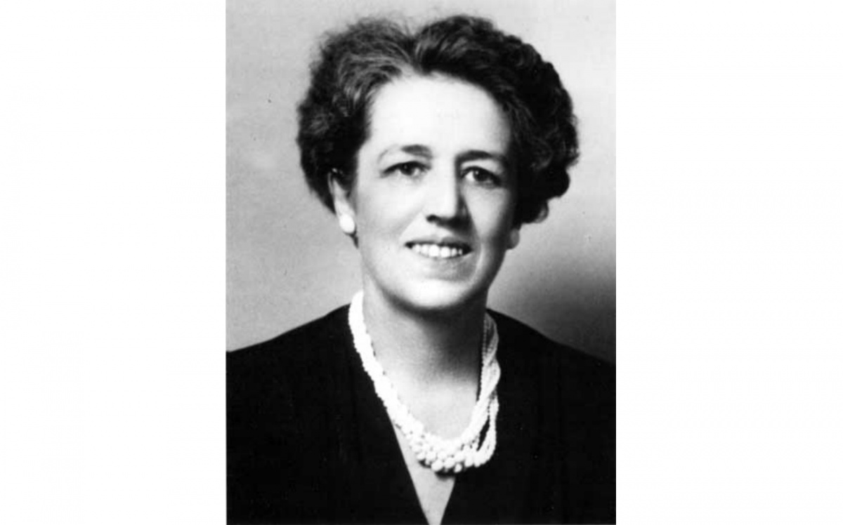 A black and white head shot of a woman, Gertrude S. Cooper, smiling and wearing a black top and white necklace.