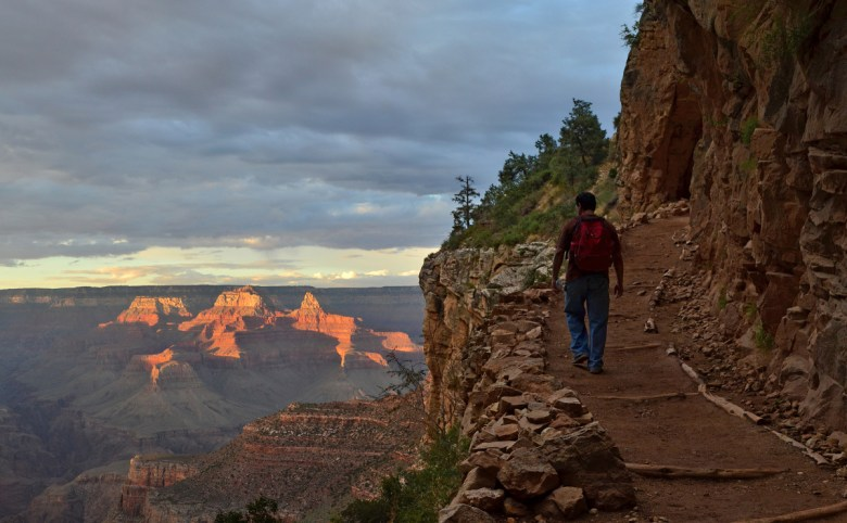A man wearing a backpack walks along a dirt trail overlooking a massive canyon.