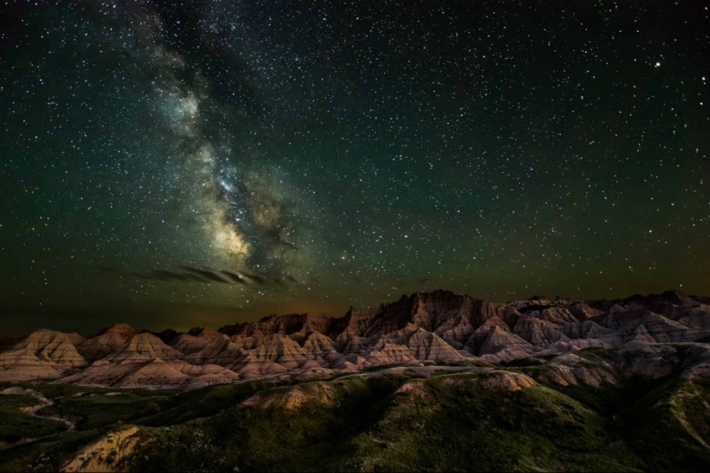 The milky way and a night sky full of stars hangs over a landscape of low rugged rock formations.