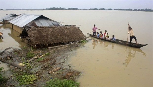 Flood-affected local residents move to safer places on a boat after heavy rains at Jajimukh village