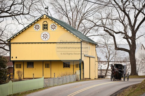 Traditional Amish horse buggy passes an Amish barn with hex sign Mascot, PA