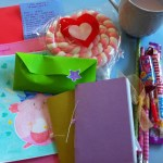 A photograph of a collection of colourful envelopes, handwritten letters and sweets against a blue background