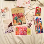 A photograph of Doll Hospital Issue One with a selection of sweets, Doll Hospital stickers, cat cards, and a mix tape laid across a bed sheet