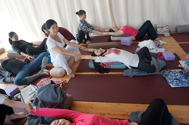 A Student demonstrating half moon pose with the pregnancy belly. The pregnancy belly is used to help simulate the size and weight of a third trimester pregnant woman. This helps us demonstrate and practice prenatal modifications.