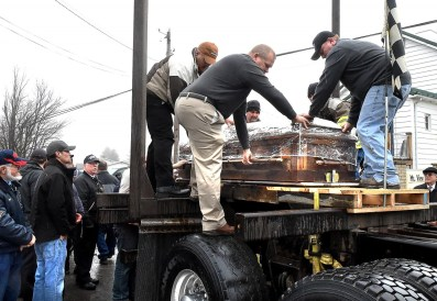 Okey Dalton is placed on logging truck after funeral Monday