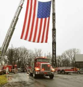 Body of Okey Dalton (background) in curve will ride under drapped flags from VFD.