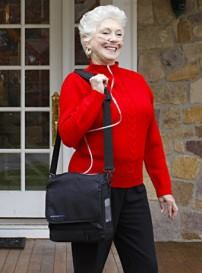 Woman using portable oxygen concentrator with continuous flow of oxygen
