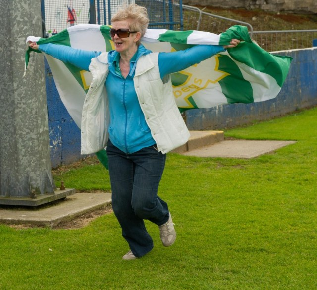 A delighted St Catherines fan leads the pitch invasion after the final whistle.  Photo Clive Wasson