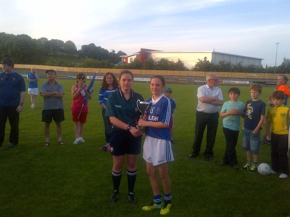 Victorious Naomh Conaill U14 captain Shana Quinn received the County A Championship trophy from referee and County Secretary Siobhan Coyle at O'Donnell Park