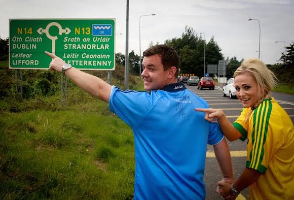 Danny O'Carroll and his wife Amanda Woods who will be supporting two different sides in this weekend semi-final between Dublin and Donegal.The couple are pictured at the roundabout near to their home in Co Donegal with Danny supporting the blues and his wife Amanda supporting Donegal as she points out Michael Murphy's signature  on the Dublin shirt. Photo Brian McDaid