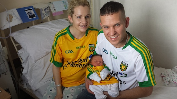 Proud parents Claire Higgins and Odhran Grant with newborn son Daithi in their Donegal jerseys.