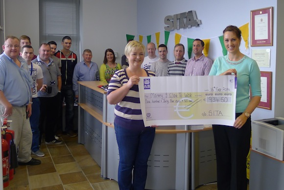 Anne Marie Doherty, the mother of 5 year old Killygordon boy Paul, is presented with a cheque for  €934.50 towards the Mammy I Want To Walk Fund from SITA staff member Leona Barron.
