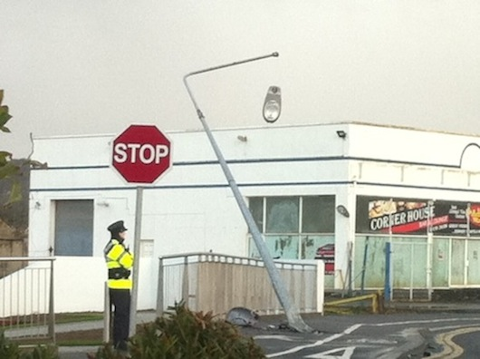 The light hangs from the ESB pole after the crash as Gardai stand watch. PIc by Donegal Daily.