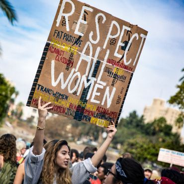 "Woman holding sign that says ""Respect All Women"""