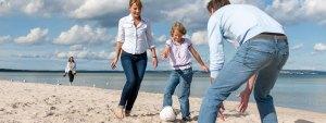 Familie, die am Strand Fußball spielt