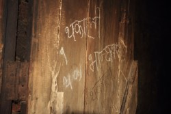 """The students living here might not have much but they do have a sense of humor! This is the door to the kitchen. The writing in chalk reads,""""Thakali Bhanchhagar."""" (""""Thakali Kitchen."""") The Thakalis are a people from north West of Pokhara and well known for their cuisine. """"Thakali Bhanchhaghar"""" is the name of a popular restaurant."""