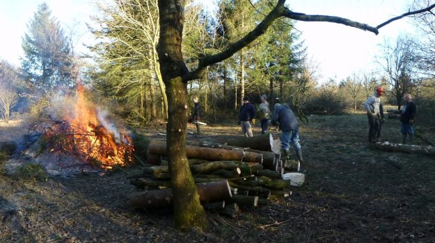 An area within a wood cleared of trees, with a fire burning and some people standing around