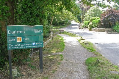 Road with sign to left announcing Durlston Country Park