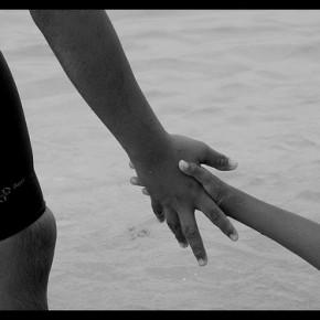 große Hand zieht kleine Hand aus dem Wasser