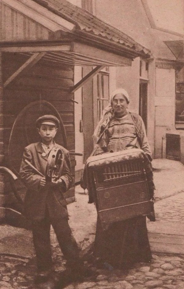 Street musicians playing barrel organ and tambourine