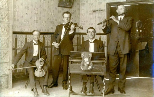 Musicians playing harmonium, violin, long neck violin, and flute.