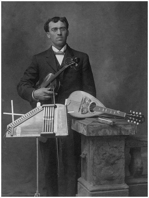 Musician with autoharp, mandolin, violin, and harmonica