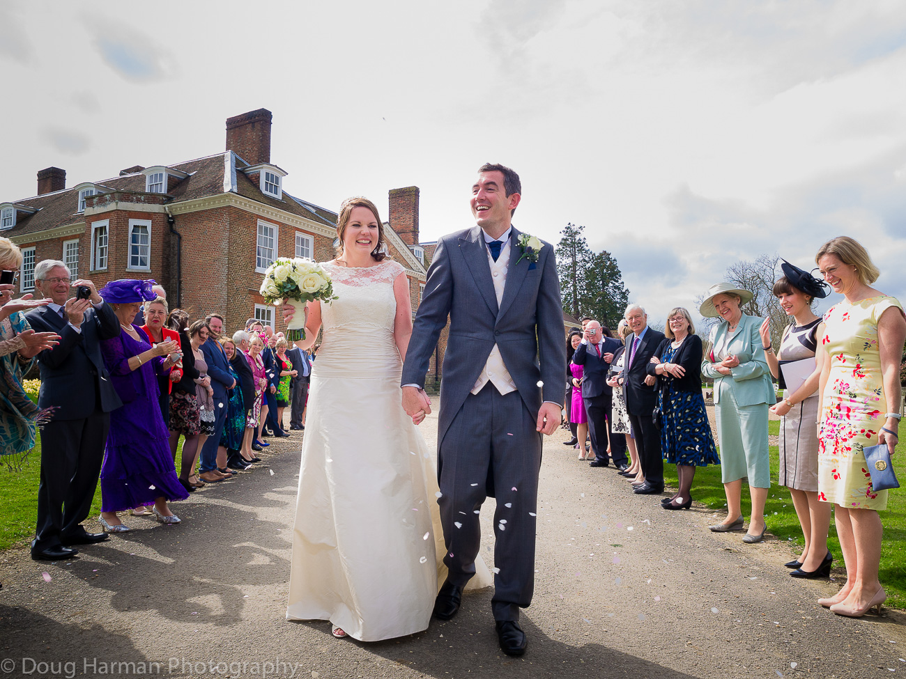Tim and Louise Carter celebrate as gusts throw confetti on the occasion of their wedding, at Chilston Park Hotel, near Lenham.