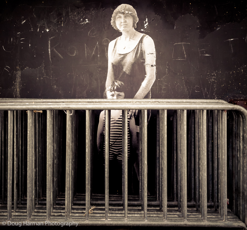 Mother and Son: A mural in Dunkirk, France with railings.