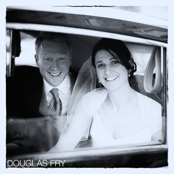 Photograph of bride and groom leaving the church by car - black and white image