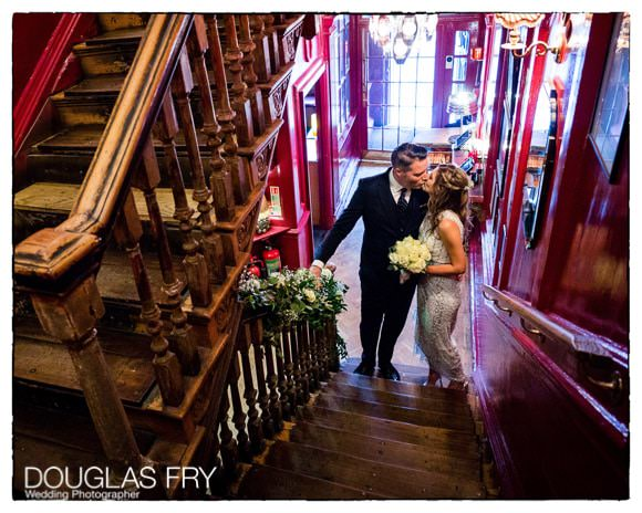 Bride and groom kissing on staircase in Union Club