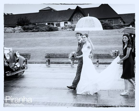Bride and groom in black and white approaching car to travel to reception